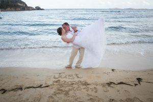 groom dips bride on the beach in st thomas